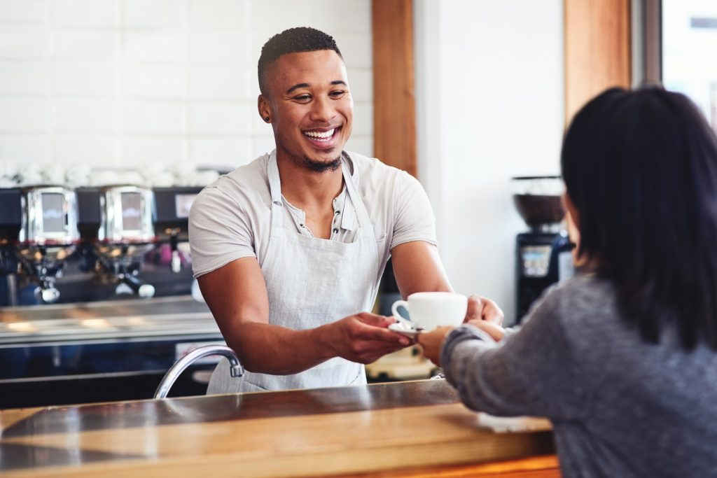 Shot of a young barista serving a cup of coffee to a customer in a cafe representing your coffee service staff