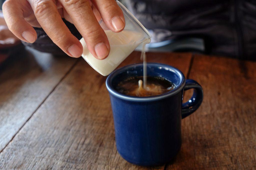 representing non-dairy creamers, someone pouring a creamer into coffee