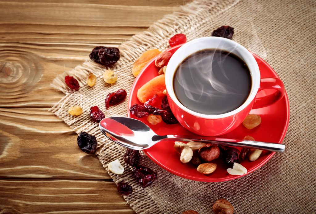 a coffee mug of coffee with nuts and fruit around it representing coffee flavoring